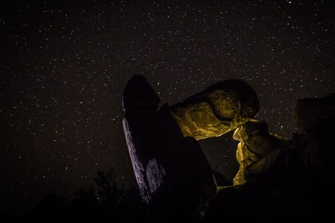 A yellow light dimly illuminated large rocks, with the night sky highlighted in the background.