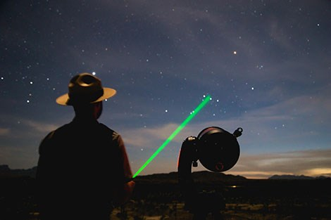A ranger stands next to a telescope, with a laser pointer shooting towards a stat.