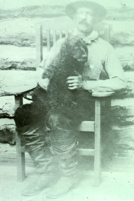 Doc Barry sitting on the porch in a rocking chair with a black dog on his lap.