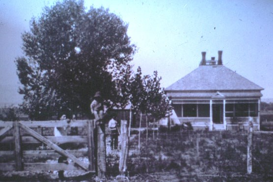 A child sits on the gate in this historic photo of Henry Clay Lovell's home on the ML ranch