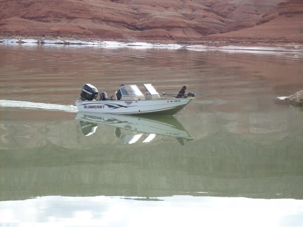 Fisherman in his boat at the red cliffs area near Horseshoe Bend