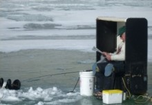 Ice fisherman waiting for a strike on his line