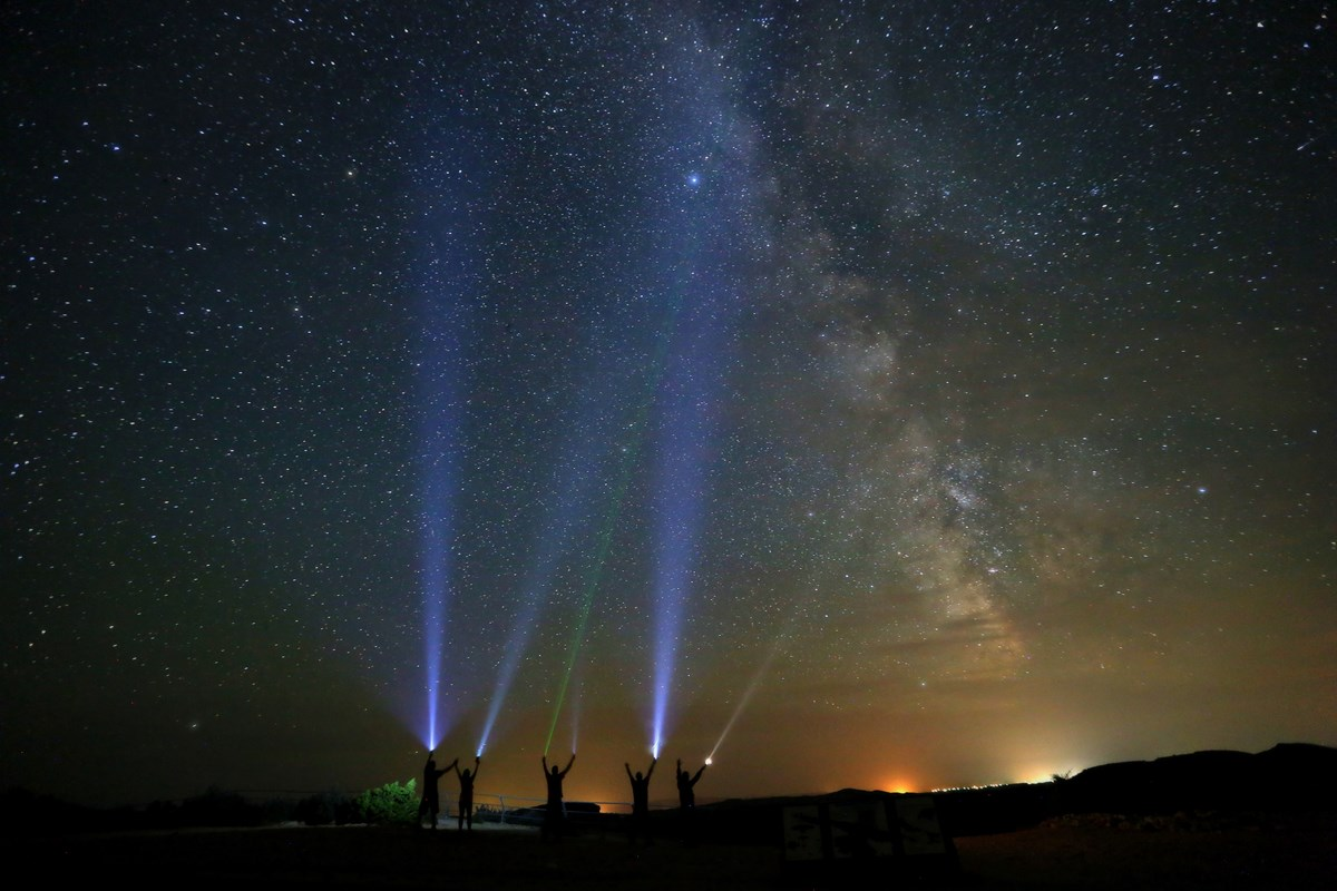 5 people shine flashlights into the night sky at Devil Canyon Overlook.