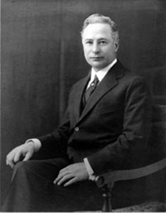 A black and white image of Barron Collier sitting in a chair.