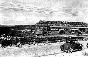 The H.W. Bird Tomato Corporation packing facility, along Birdon Road. Black and white images featuring an antique car parked on a dirt road overlooking the skeletal structure of a packing facility.