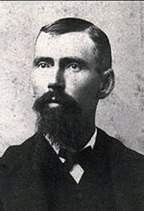 A black and white bust of Charles Torrey Simpson with a large goatee and a bow-tie.