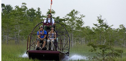 Three people ride on an air-boat in a wetland prairie.