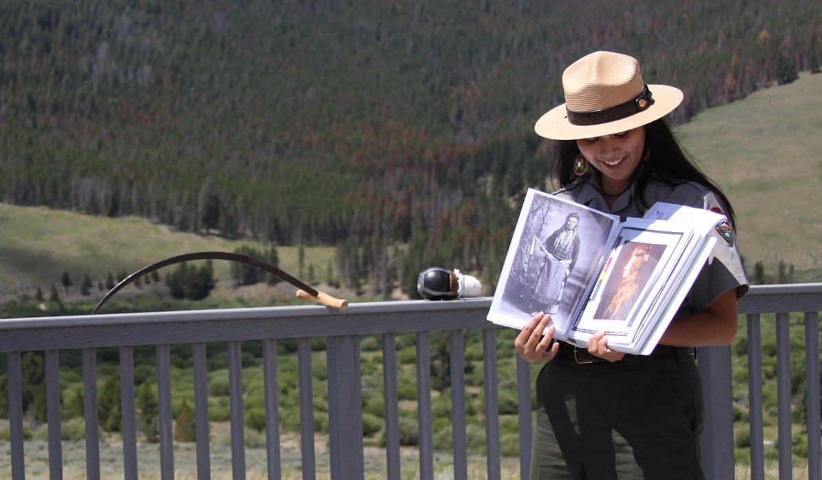 A female park ranger standing on a deck overlooking the hillside and valley where the Big Hole battle took place in 1877 is sharing photos of Nez Perce.