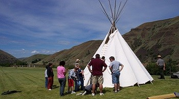 A group of people help two rangers set up a tipi.