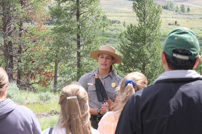 A crowd stands in a forest with their backs to the camera and facing a female park ranger who is holding a rice trowel bayonette up for all to see.