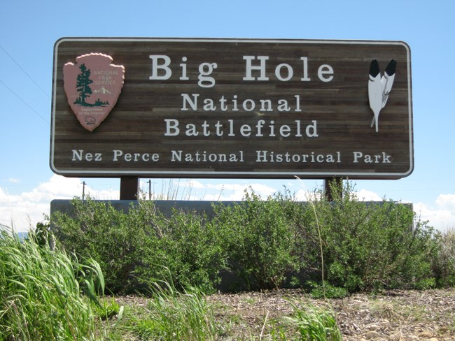 "A wooden sign with the words ""Big Hole National Battlefield Nez Perce National Historic Park"" carved onto it."