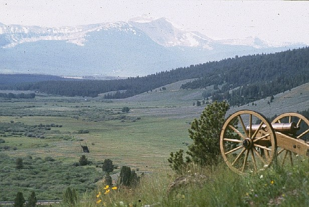 A mountain howitzer on hill overlooking a valley and the mountains.