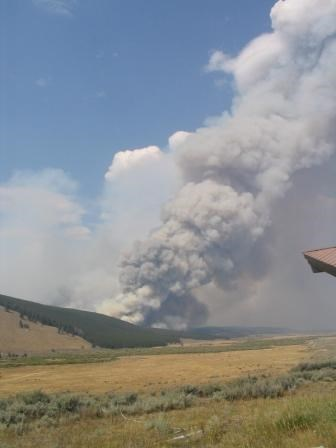 A field with a plume of smoke in the distance.