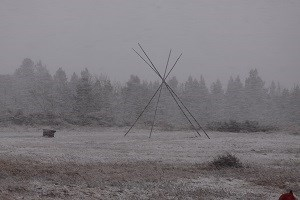 Tepee poles with trees in the distance during snow storm.