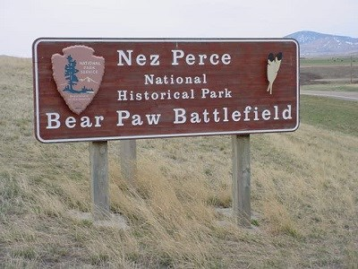 "Wooden sign with  the National Park Service Arrowhead logo and the words ""Nez Perce National Historical Park Bear Paw Battlefield"" carved into it."
