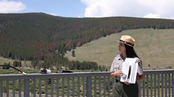 A female park ranger shares information on a deck overlooking a valley and partially forested hillside.