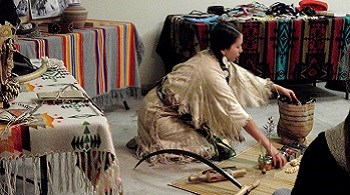 A Nez Perce woman wearing traditional clothes kneels on floor surrounded by baskets and other cultural items.