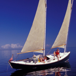 Three people in a sailboat on calm seas