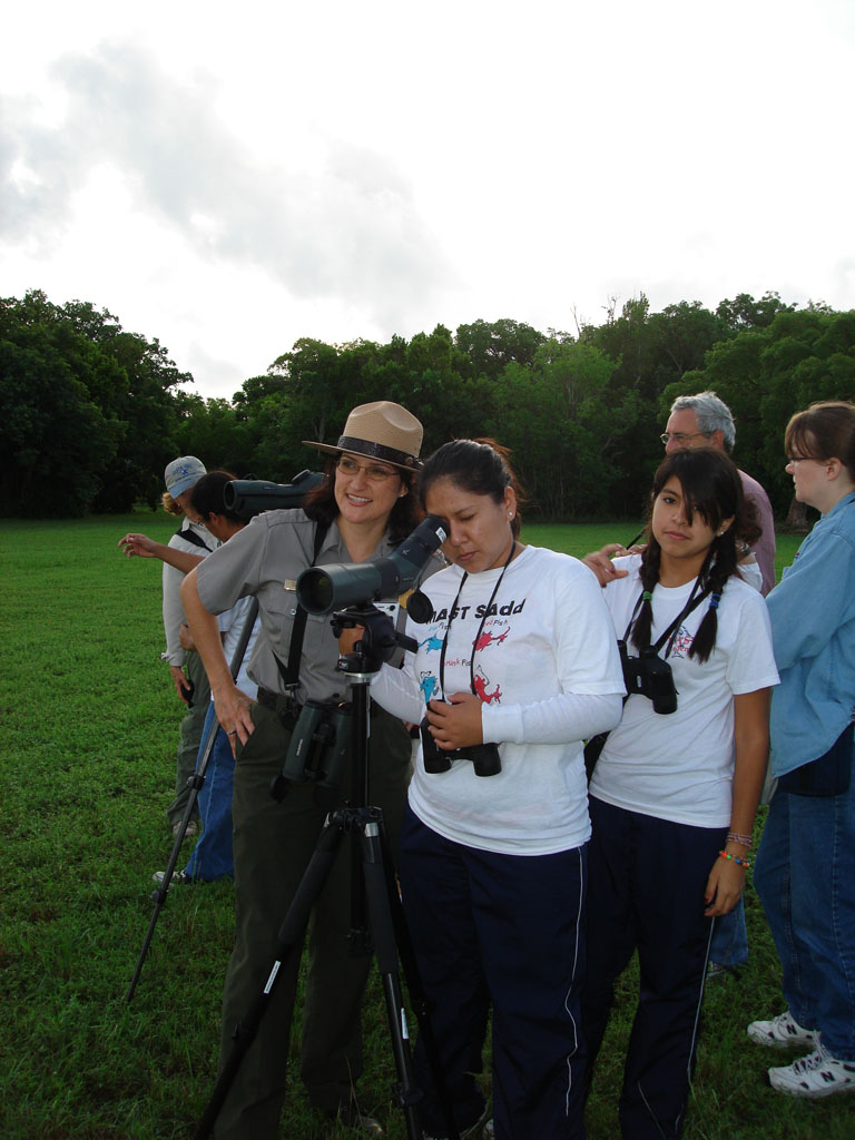 A park ranger shows a visitor how to use a spotting scope