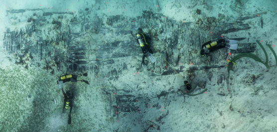 Divers float over the exposed timbers of the wreck of HMS Fowey.