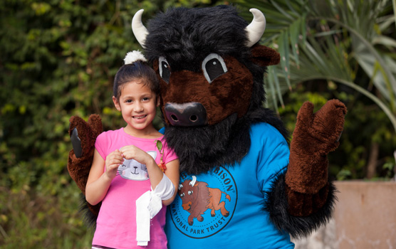 Buddy Bison Poses with a young park visitor.