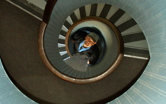 A man looks up from the bottom of the circular stairway in Cabrillo National Monument's Point Loma lighthouse.