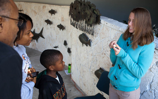 A park volunteer teaches a family about cone snails.