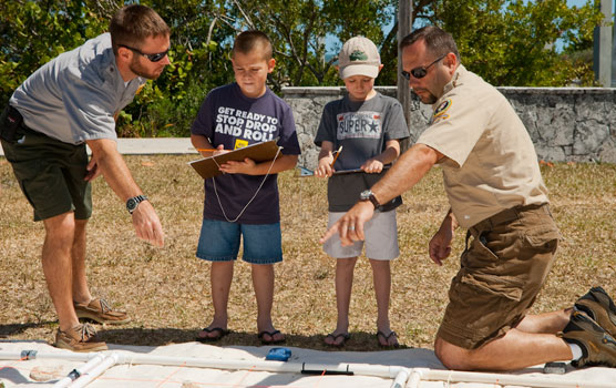 Two Family Fun Fest staffers help two participants map a mock shipwreck.