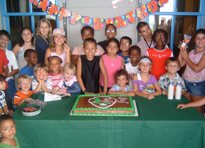 Smiling children surround a birthday cake featuring the National Park Service arrowhead symbol.