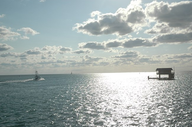 Morning in Stiltsville, a boat heading towards open water.