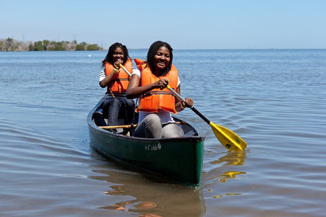 Two girls wearing orange life vests paddling in a canoe