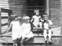Small children sitting on a front porch.