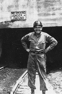 Cack Slaven stands in front of a mine opening.