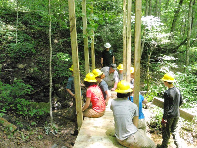 A group of young adults working together to rebuild a bridge on a trail