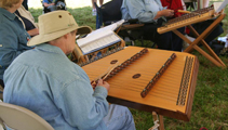 man with hat playing dulcimer with group