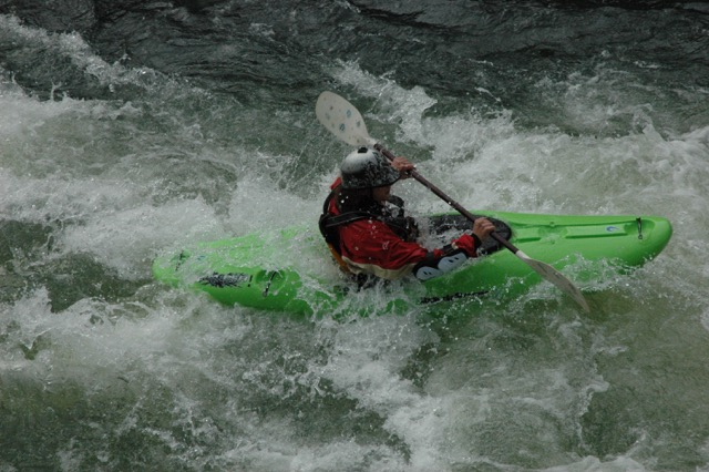 Kayaker maneuvering through rapids in river