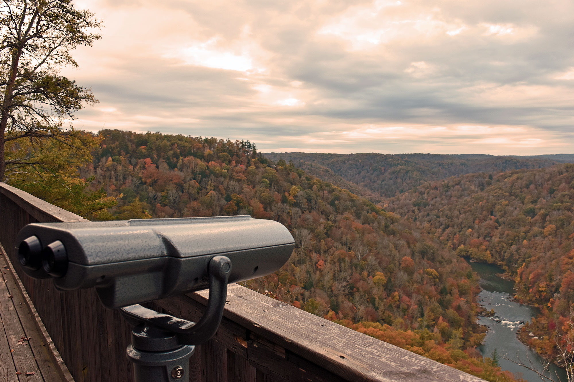 Viewfinder points over the overlook towards the river and multi-colored forests below