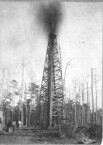 historic photo gushing oil derrick with workers standing nearby