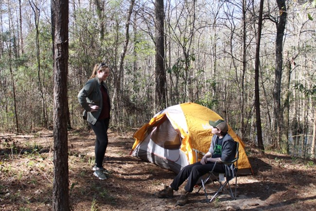 1 person standing and 1 person sitting outside of a tent in the woods