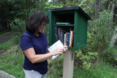 woman reading a book from little free library