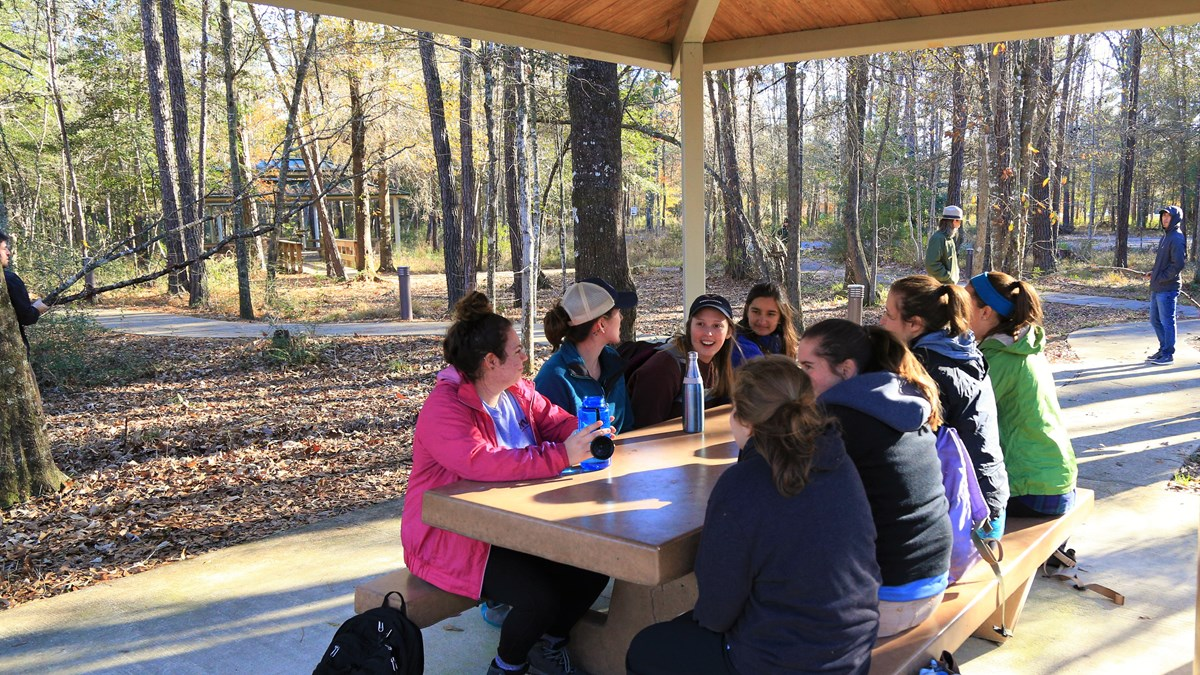 group of people sitting a picnic table in the visitor center's picnic area