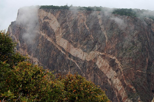thick pink stripes of pegmatite in a large cliff face, fog