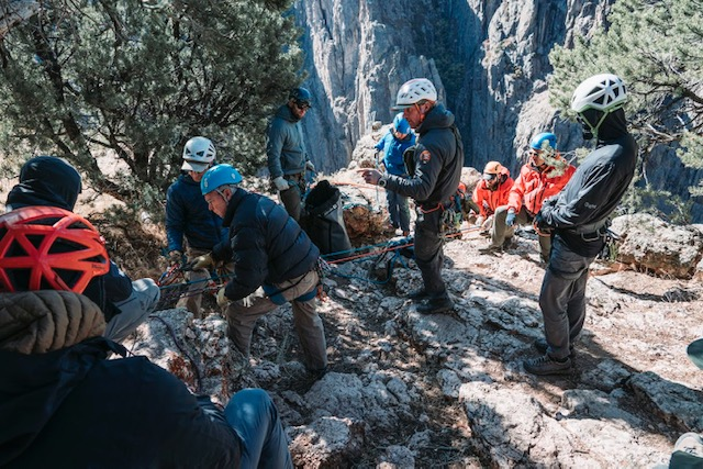 rescue team at top of dramatic canyon prepare ropes for rescue