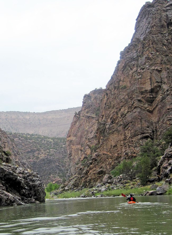 kayaker paddling on calm river water with dark canyon walls on both sides