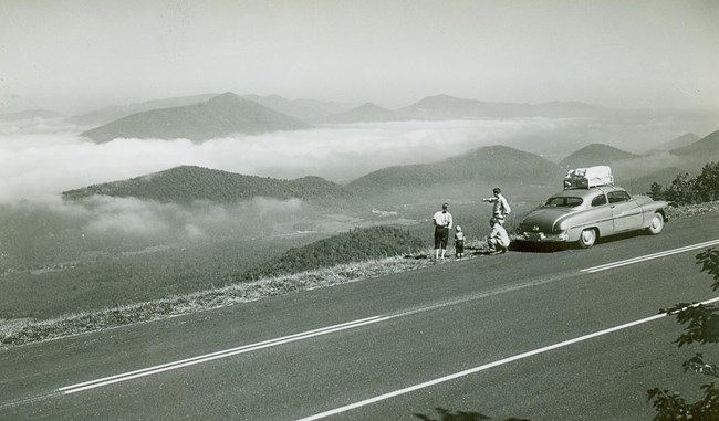 A family in a mid-1900s automobile stopped at an overlook to enjoy the scenery