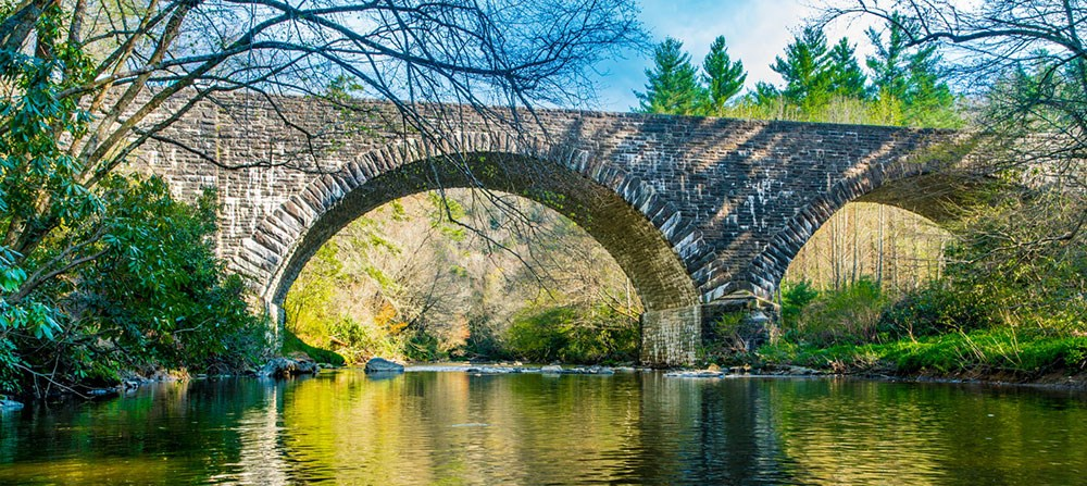 The high arches of Linville River Bridge rise above the sparkling river below.