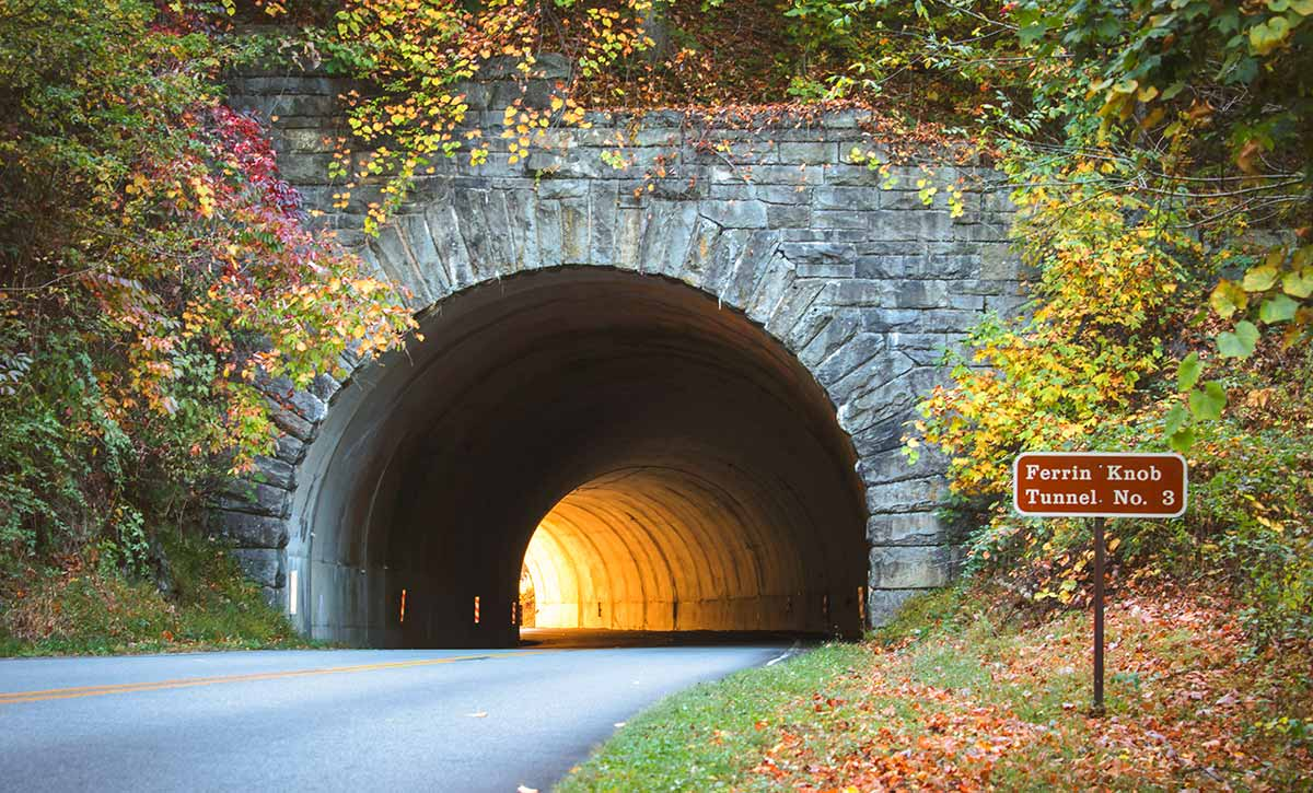 Sunlight illuminates the far end of a stone tunnel on the parkway. Red and yellow fall foliage surrounds the tunnel entrance.