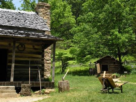 A log cabin surrounded by a yard and forest at Humpback Rocks Farm.