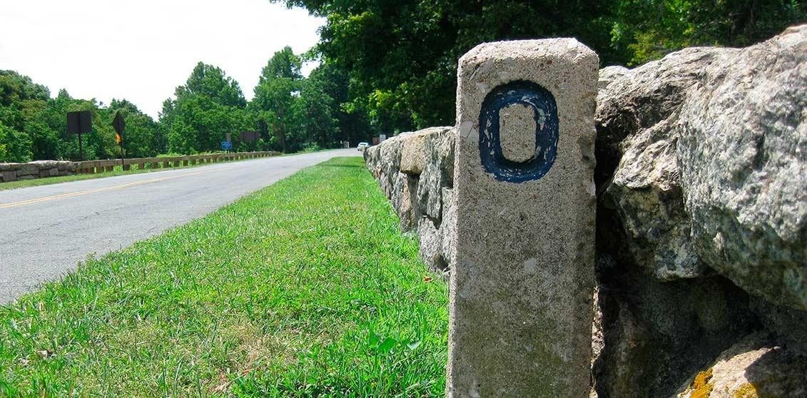 A concrete milepost marker with a 0 on it marks the beginning of the parkway in Virginia