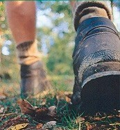 Close up shot of a hiker's boots as he walks on a trail